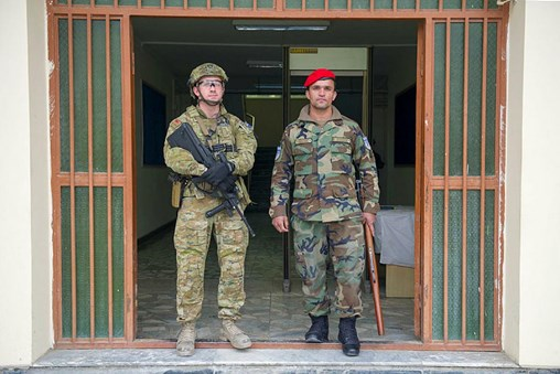 Australian Army soldier Private Jack Reynolds of the Force Protection Element and a Afghan National Army soldier stand guard outside the Kabul Garrison Command.