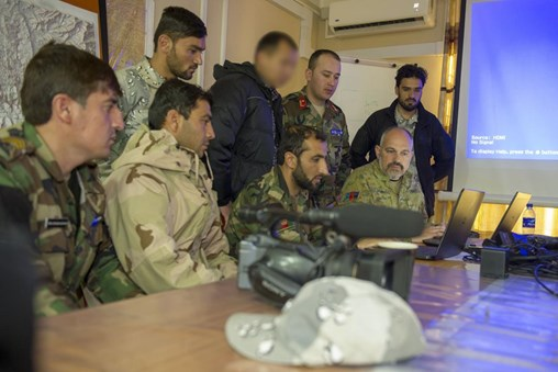 Afghan members of the Kabul Garrison Command public affairs unit watch a video editing session with Royal Australian Navy Petty Officer Andrew Dakin.