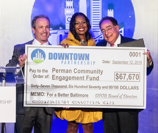 Kirby Fowler, Shelonda Stokes and Jay Perman hold a ceremonial check for the Perman Community Engagement Fund
