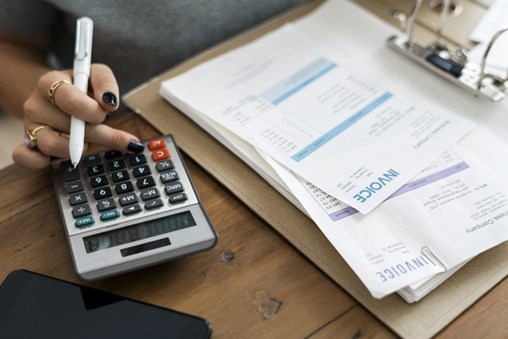woman using calculator to determine budget