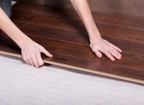 A person laying down flooring.