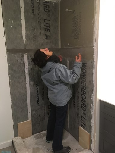 Susie standing in the roughed out shower envisioning what's to come.