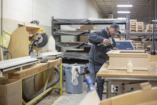 A NuWood employee assembling a custom order