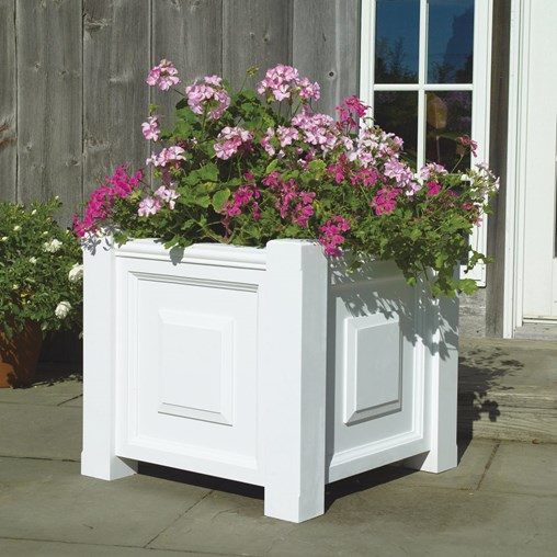 A lovely array of pink flowers grows in this Paneled Planter.