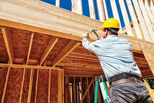 Builder hammering framing