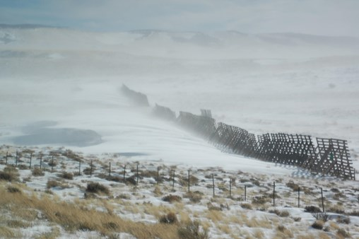 A snow fence in the wind.