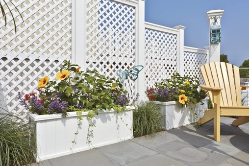 Privacy with charm and imagination are shown here by the smart combination of stepped crisscross lattice panels fronted by Walpole Rockport planters.