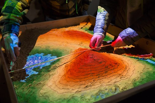 Students working with augmented reality sandbox