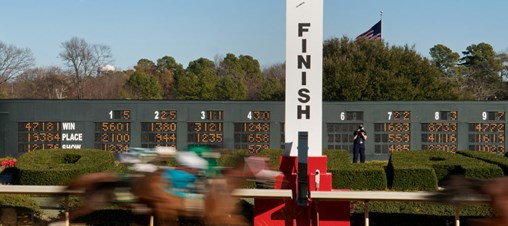 Rapid motion photo of horses at a race track finish line