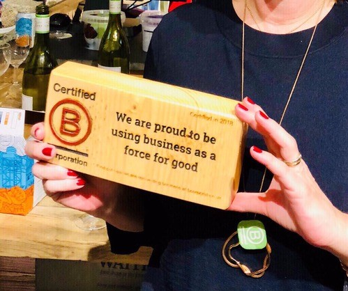 Liz the Chief Happiness Officer holding the B Corp block