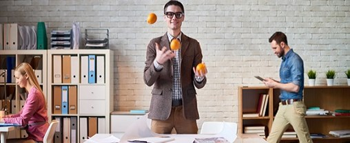 Young man juggling oranges as easier as he can cope with any task